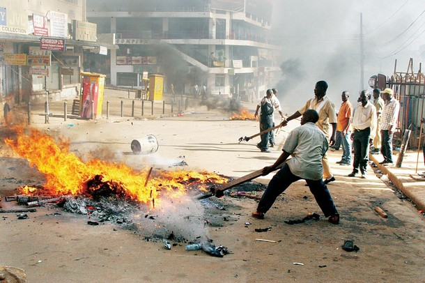 A crowd attempts to put out a fire on a street in Kamapala