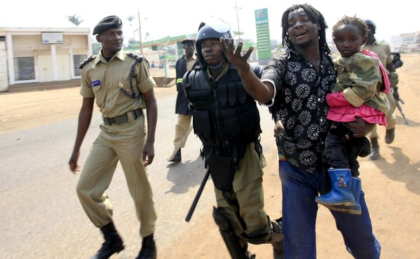 Ugandan police arrest a man carrying a child at a suburb of Kampala September 11, 2009. Gunshots rang out in the Ugandan capital Kampala