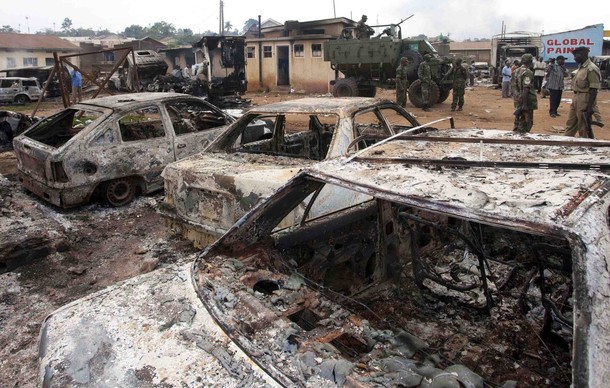 Ugandan soldiers and policemen guard a burnt police station and vehicles in a suburb of Kampala