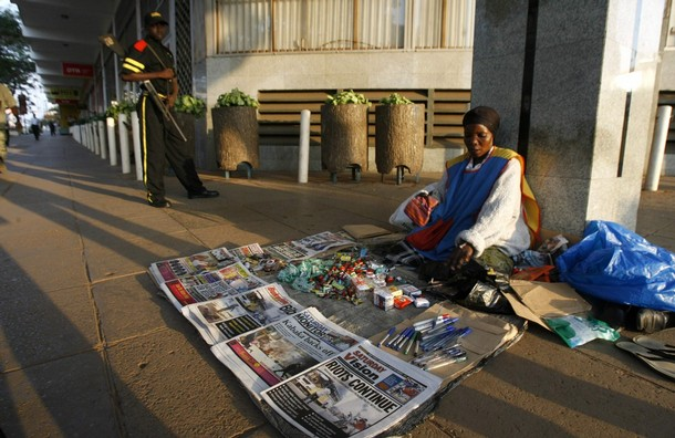 A newspaper vendor sells newspapers reporting on the ongoing riots and violence resulting from a row between the government and the kingdom of Buganda, along the streets of Uganda's capital Kampala