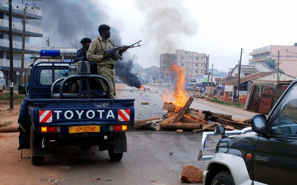 Ugandan police ride on the back of a pick-up truck past burning barricades in the Natete suburb of Kampala