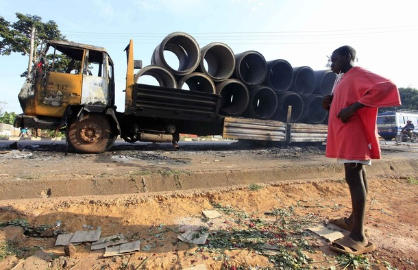 A boy looks at the remains of a burnt truck following clashes in the Seta neighbourhood of the Ugandan capital Kampala