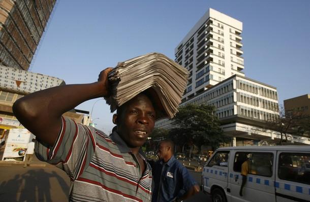 A vendor carries newspapers for sale along the streets of Uganda's capital Kampala