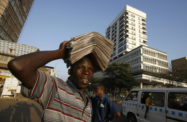 A vendor carries newspapers for sale along the streets of Uganda's capital Kampala
