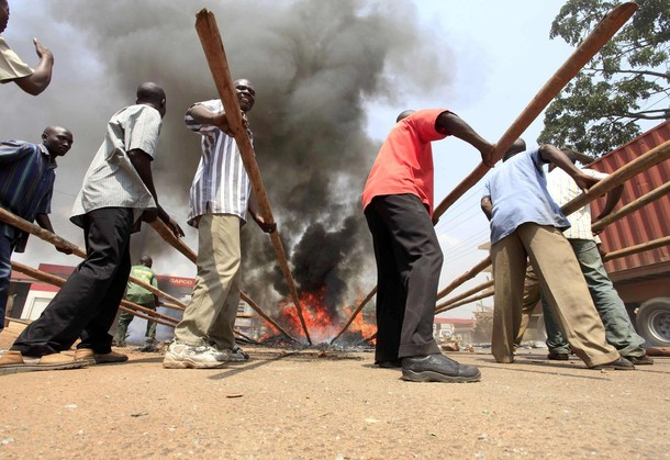 Rioters clear burning tyres used to block roads in a suburb of Kampala