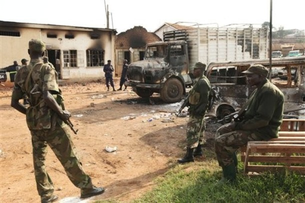 Armed riot police secure the area around the razed Nateete Police Station in Kampala, Uganda