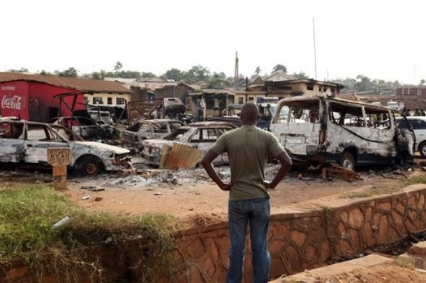 A Ugandan man surveys the area with destroyed cars around the destroyed Nateete Police Station in Kampala
