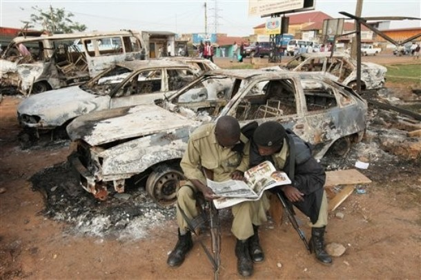 Armed riot police read a newspaper report as they sit among the destroyed cars near to the destroyed Nateete Police Station in Kampala, Uganda