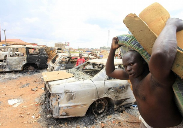 Looting in the Name of King and Tribe. A suspected looter carries mattresses after his arrest following clashes in the Natete neighbourhood in the Ugandan capital Kampala