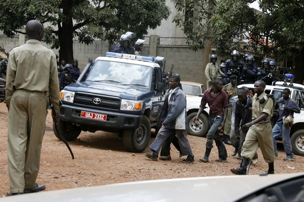Ugandan police escort arrested civilians into the Wandegeya police station in the capital Kampala