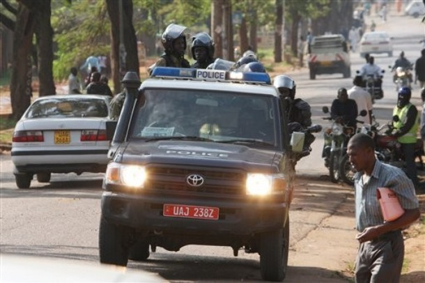 Ugandan armed police in a vehicle patrol a street in Kampala, Uganda