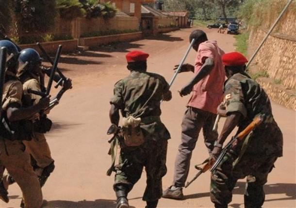Members of the Ugandan military and police beat  a demonstrator in Uganda's capital city Kampala