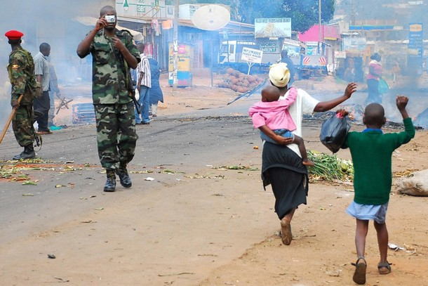 Residents of Kasubi suburb west of Kampala raise their hands as they walk past riot policemen