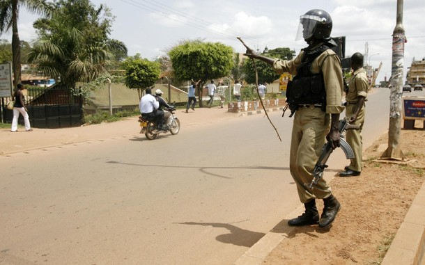 Ugandan police instruct residents to run along a Wandegeya street in the capital Kampala