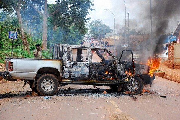 A Ugandan policeman takes photos of a burning car in the Kasubi suburb, west of Kampala, Uganda