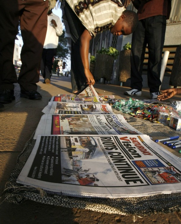 A pedestrian reads newspapers, displayed by a vendor, reporting on the ongoing riots and violence resulting from a row between the government and the kingdom of Buganda