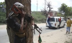 A Sufi fighter stands guard behind a tree outside their military base near Bakara market in Somalia's capital Mogadishu