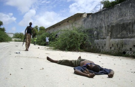 An unidentified gunman walks towards the body of a man killed during clashes between Islamist insurgents and Somalia government troops in south Mogadishu