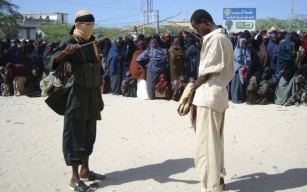 An Islamist fighter from Hisbul Mujaahidin uses a stick to beat one of their members convicted of chewing khat, a narcotic leaf, in Somalia's capital Mogadishu