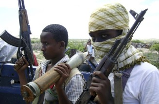 Fighters loyal to Hisbul Islam party carry their weapons as they patrol the outskirts of Mogadishu
