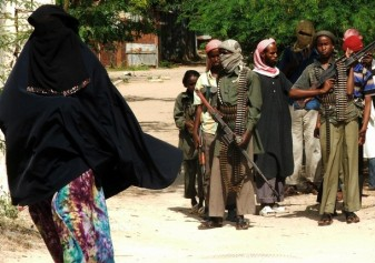 A veiled Somali woman walks past hardline Islamist militants in Somalia's capital Mogadishu