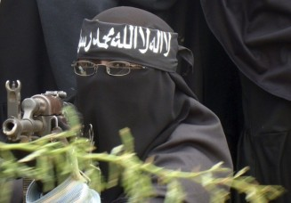 A female Al Shabaab fighter points a gun during a demonstration against AMISOM in Suqaholaha neighborhood, north of Mogadishu