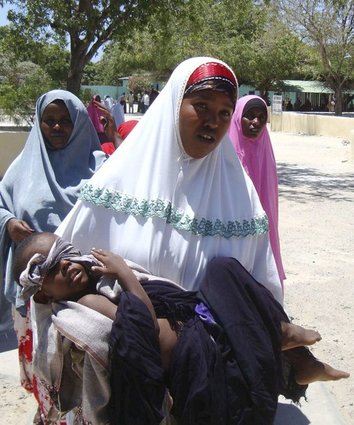 A woman carries a child wounded during clashes between AU peacekeepers and Islamist rebels in Somalia's capital Mogadishu