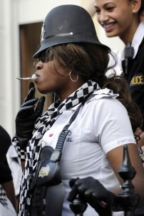 A woman dressed as a British policewoman, smokes at the annual Notting Hill Carnival street party in London