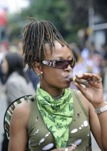 A woman smokes her cigar at the annual Notting Hill Carnival street party in London